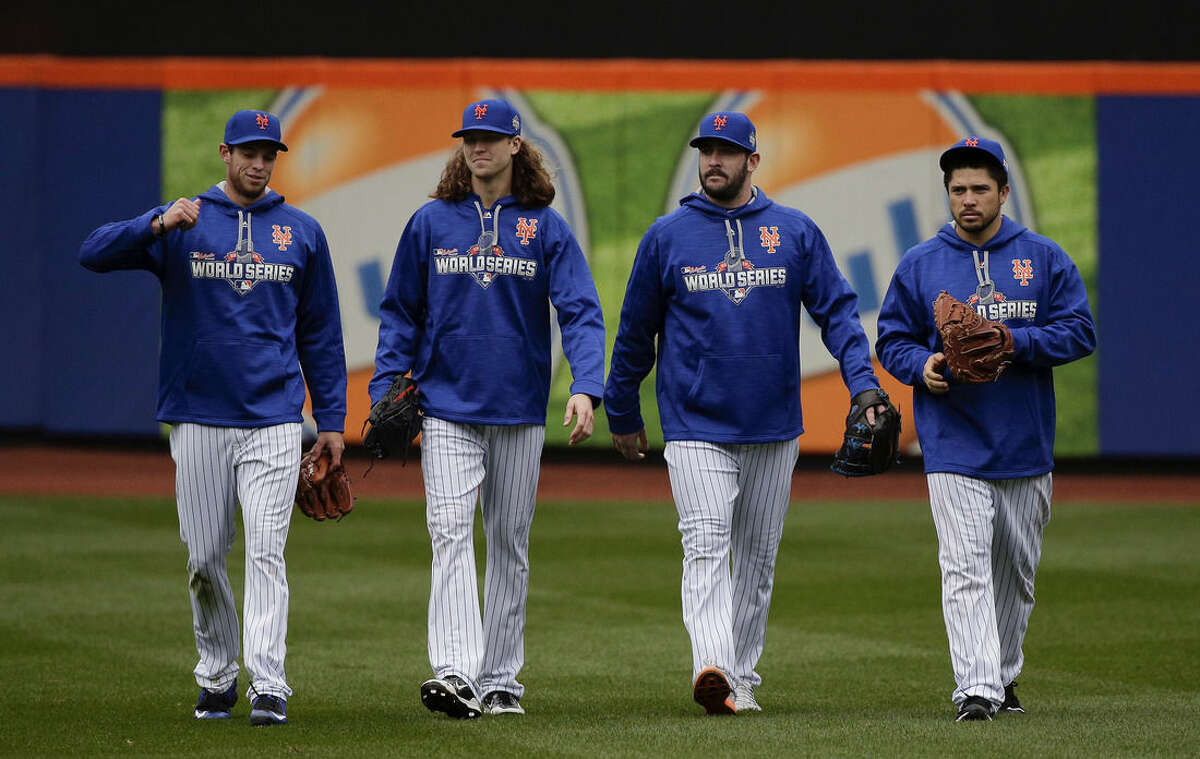 From left, New York Mets pitchers Steven Matz, Jacob deGrom and Matt Harvey and catcher Travis d'Arnaud walk off the field at the end of batting practice, Saturday, Oct. 24, 2015, in New York. The Mets will face the Kansas City Royals in Game 1 of the World Series on Tuesday. (AP Photo/Julie Jacobson)