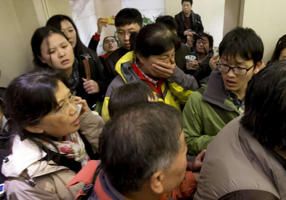 A woman, center, surrounded by media covers her mouth on her arrival at a hotel which is prepared for relatives or friends of passengers aboard a missing airline, in Beijing, China Saturday, March 8, 2014. A Malaysia Airlines Boeing 777-200 carrying 239 people lost contact over the South China Sea early Saturday morning on a flight from Kuala Lumpur to Beijing, and international aviation authorities still hadn't located the jetliner several hours later. (AP Photo/Andy Wong)