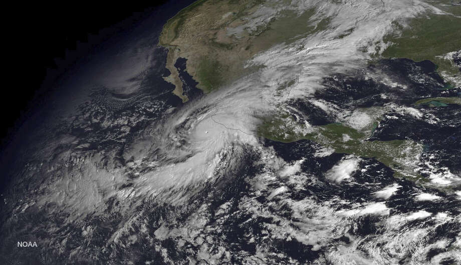 """This satellite image taken at 10:45 a.m. EDT on Friday, Oct. 23, 2015, and released by the National Oceanic and Atmospheric Administration shows Hurricane Patricia moving over Mexico's Pacific Coast. Hurricane Patricia headed toward southwestern Mexico Friday as a monster Category 5 storm, the strongest ever in the Western Hemisphere that forecasters said could make a """"potentially catastrophic landfall"""" later in the day. (NOAA via AP)"""