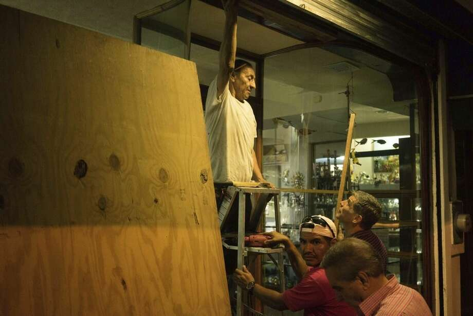"People preparing for the arrival of Hurricane Patricia board up a souvenir shop in the Pacific resort city Puerto Vallarta, Mexico, Thursday, Oct. 22, 2015. Patricia headed toward southwestern Mexico Friday as a monster Category 5 storm, the strongest ever in the Western Hemisphere that forecasters said could make a ""potentially catastrophic landfall"" later in the day. (AP Photo/Cesar Rodriguez)"
