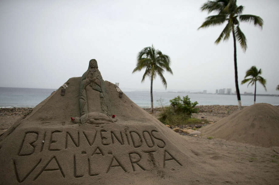 "A sand sculpture carved with a message that reads in Spanish; ""Welcome to Vallarta"" decorates the beach in Puerto Vallarta, Mexico, Friday, Oct. 23, 2015. Patricia barreled toward southwestern Mexico Friday as a monster Category 5 storm, the strongest ever in the Western Hemisphere. Locals and tourists were either hunkering down or trying to make last-minute escapes ahead of what forecasters called a ""potentially catastrophic landfall"" later in the day. (AP Photo/Rebecca Blackwell)"