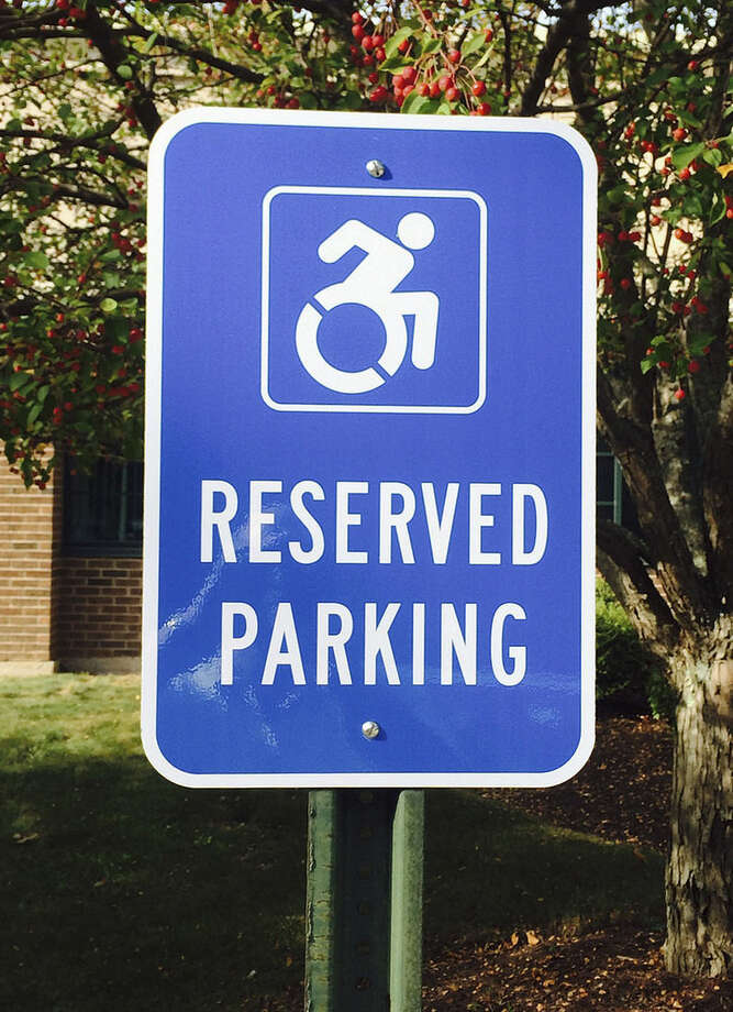 In this Friday, Sept. 25, 2015 photo provided by Favarh, The Arc of the Farmington Valley, a modernized handicapped sign designates a reserved space in a parking lot in Canton, Conn. Advocates want to replace the familiar image of a stick figure in a wheelchair with the action-oriented logo to emphasize ability, not disability. (Bill Neagus/Favarh, The Arc of the Farmington Valley via AP)