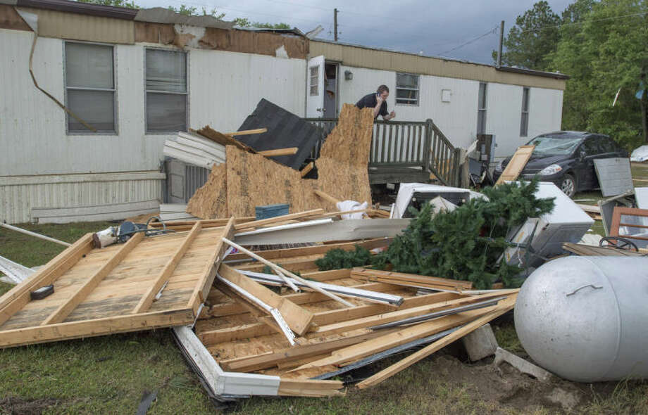 Ray Harvey talks on his cell phone while looking over the storm damage to the rear of his mobile home near Stedman, N.C., Tuesday, April 29, 2014. At least five counties in eastern North Carolina reported tornadoes on Tuesday. (AP Photo/The Fayetteville Observer, Johnny Horne)