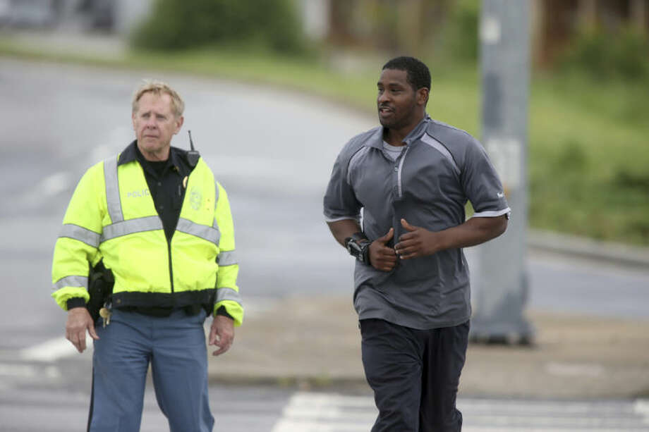 A Cobb County Police officer, left, escorts a FedEx employee as he crosses McCollum Parkway leaving the blocked off area after an early morning workplace shooting at the Airport Road FedEx facility Tuesday April 29, 2014, in Kennesaw, Ga. A shooter opened fire at a FedEx center wounding at least six people before police swarmed the facility. The shooter was found dead from an apparent self-inflicted gunshot wound. (AP Photo/Jason Getz)