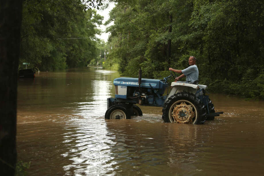 Howard Lifson rides his tractor down Ferry Road to check on his boat during flooding on the Fish River which crested to historic levels following heavy rain on Wednesday, April 30, 2014 in south Baldwin County, Ala. (AP Photo/ AL.com, Sharon Steinmann)