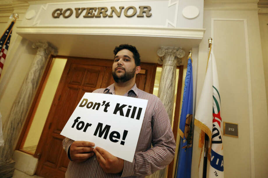 AP Photo/The Oklahoman, Steve GoochHossein Dabiri with Oklahoma Coalition Against the Death Penalty holds a sign protesting the death penalty at the State Capitol in Oklahoma City, Tuesday April 29.