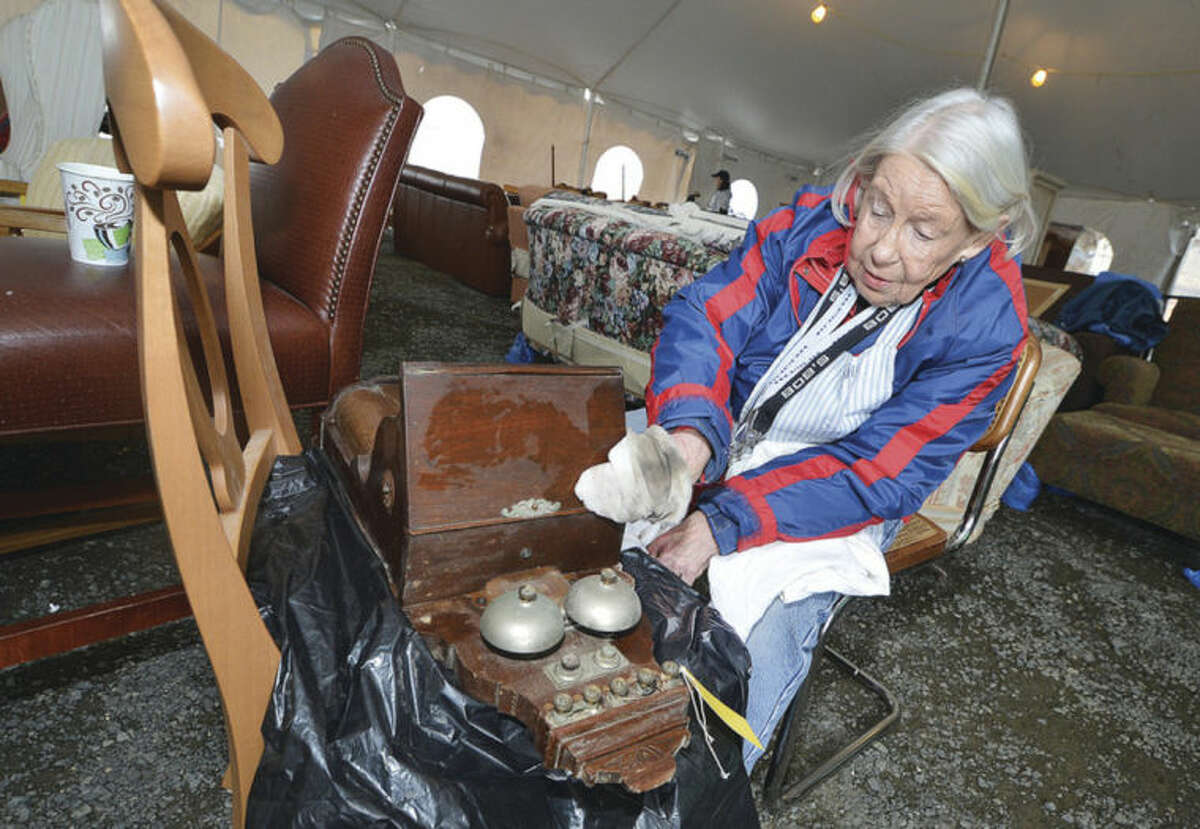 Judy Hitter dusts off a vintage turn of the century hand crank wall phone up for sale at Wilton's Minks to Sinks Sale.