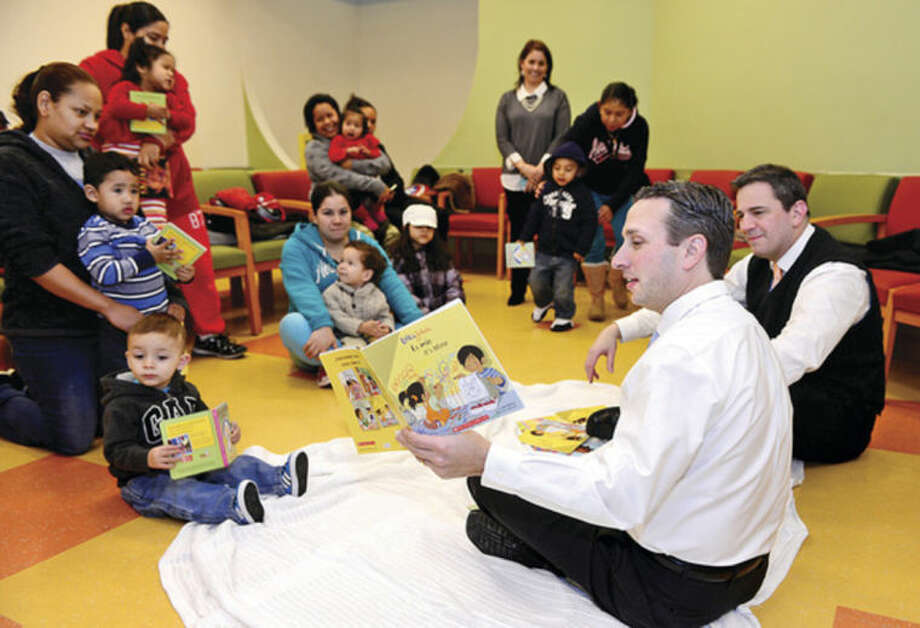 Hour photo / Erik TrautmannState Sen. Bob Duff and State Rep. Chris Perone read to children as part of the Norwalk Community Health Center's Reach Out and Read program Thursday.