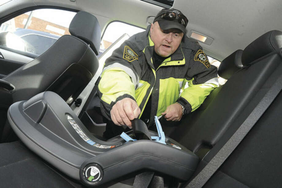 Hour photo/Matthew VinciNorwalk police officer John Haggerty installs a baby car seat Monday at the Police Headquarters. Police encourage parents to have the seat professionally installed and give step by step demonstrations and advice as they put the seats in.