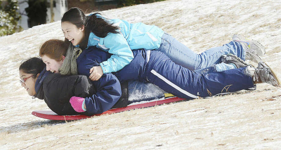 North Carolina School of Science and Mathematics' students Lucy Su, top, Gabrielle Beaudry, center, and Luckshume Ketheeswaran slide down a hill at the Hillsndale Golf Course in Durham N.C. on Wednesday, Jan. 29, 2014. A rare snowstorm left thousands across the U.S. South frozen in their tracks, with workers sleeping in their offices, students camping in their schools, and commuters abandoning cars along the highway to seek shelter in churches or even grocery stores. (AP Photo/The Herald-Sun, Bernard Thomas)