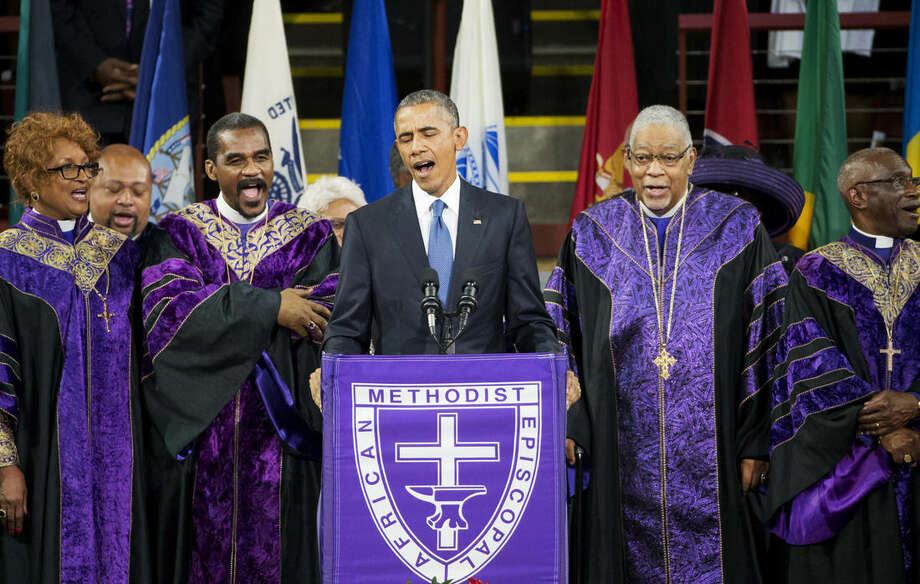 """FILE - In this June 26, 2015 file photo, President Barack Obama sings """"Amazing Grace"""" during services honoring the life of Rev. Clementa Pinckney, at the College of Charleston TD Arena in Charleston, S.C.. Pinckney was one of the nine people killed in the shooting at Emanuel AME Church last week in Charleston. The president is now staring down 11 months before his successor is chosen in an election shaping up to be a referendum on his leadership at home and abroad. He stirs deep anger among many Republicans, a constant reminder of his failure to make good on campaign promises to heal Washington's divisiveness. But he remains popular among Democrats and foresees a role campaigning for his party's nominee in the general election. (AP Photo/David Goldman, File)"""