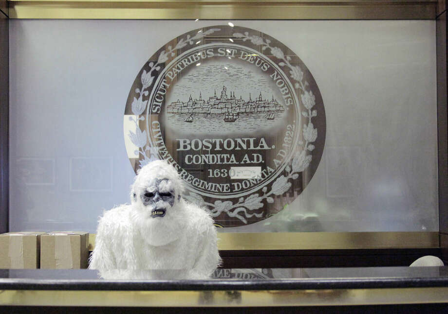 FILE - In this March 6, 2015, file photo, provided by Eric Gulliver, an anonymous creature known as The Boston Yeti poses in front of the Boston logo at City Hall in Boston. Smiles were in short supply as a series of blizzards dumped 9 feet of snow on Boston. Enter a mysterious do-gooder in an abominable snowman costume, who ran around mugging for cameras, dug out stranded drivers, gained folk hero status among winter-weary Bostonians. (Courtesy of Eric Gulliver via AP, File)