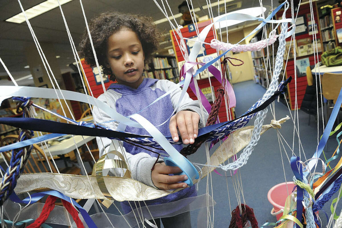 Hour photo/Matthew Vinci Olivia Hawkins, 8, contributes to the community weaving project at the Westport Library on Sunday. A large loom was created in the Children's Library and all are encouraged to weave a ribbon or fabric.