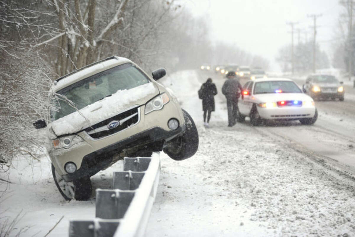 A Patton Township, Pa., police officer walks a woman to his vehicle Monday, Feb. 3, 2014, after her she slid her car off N. Atherton Street and was stranded on top of a guard rail. A winter storm in Centre County Monday caused heavy snowfall and dangerous travel conditions. (AP Photo/Centre Daily Times,Nabil K. Mark) MANDATORY CREDIT; MAGS OUT