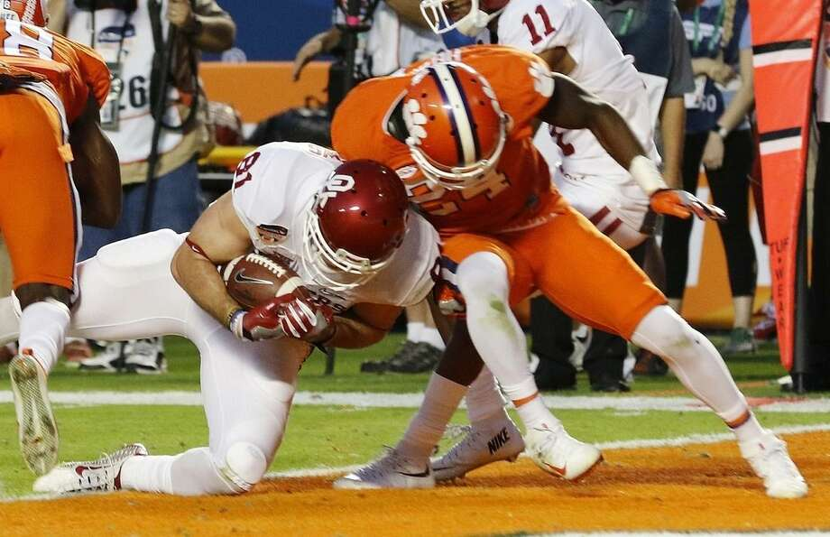 Oklahoma tight end Mark Andrews (81) scores a touchdown as Clemson linebacker Kendall Joseph (34) attempts to stop him, during the first half of the Orange Bowl NCAA college football semifinal playoff game, Thursday, Dec. 31, 2015, in Miami Gardens, Fla. (AP Photo/Joe Skipper)
