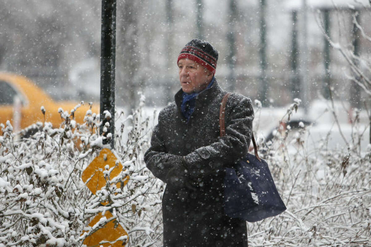 A man waits for the bus as wet snow falls Monday, Feb. 3, 2014, in New York. The National Weather Service says the storm could bring up to 8 inches of snow Monday to New York. (AP Photo/Jason DeCrow)