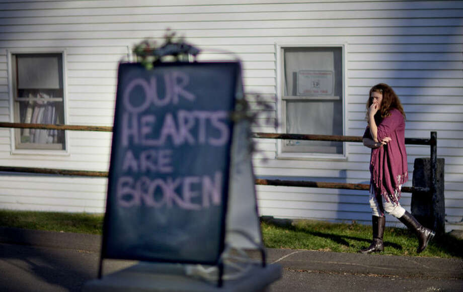 FILE - In this Dec. 15, 2012 file photo, shop owner Tamara Doherty paces outside her store just down the road from Sandy Hook Elementary School in Newtown, Conn. Although still relatively rare, thereÕs been no real reduction in the number of school shootings since security was beefed up around the country with measures such as safety drills and the hiring of police officers. (AP Photo/David Goldman, File)