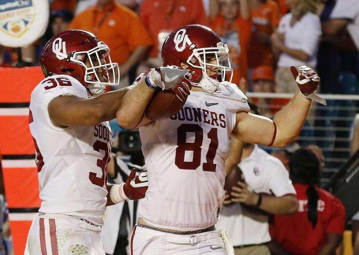 Oklahoma fullback Dimitri Flowers (36) congratulates Oklahoma tight end Mark Andrews (81) after Andrews scored a touchdown during the first half of the Orange Bowl NCAA college football semifinal playoff game against Clemson, Thursday, Dec. 31, 2015, in Miami Gardens, Fla. (AP Photo/Joe Skipper)