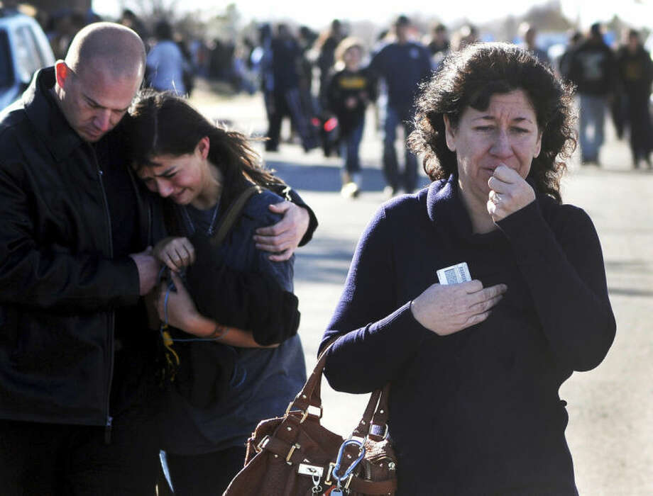 FILE - In this Jan. 14, 2014 file photo, a woman waits at a staging ground area where families are being reunited with Berrendo Middle School students after a shooting at the school in Roswell, N.M. Although still relatively rare, there?s been no real reduction in the number of school shootings since security was beefed up around the country with measures such as safety drills and the hiring of police officers, after the rampage at Connecticut's Sandy Hook Elementary School in December 2012. (AP Photo/Roswell Daily Record, Mark Wilson, File)