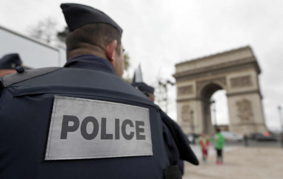 "Police forces patrol near the landmark, the Arc de Triomphe, in Paris, Tuesday, Nov. 17, 2015. France's Interior Minister Bernard Cazeneuve has said that authorities carried out ""128 police raids last night"" following Friday's deadly Paris attacks. (AP Photo/Frank Augstein)"