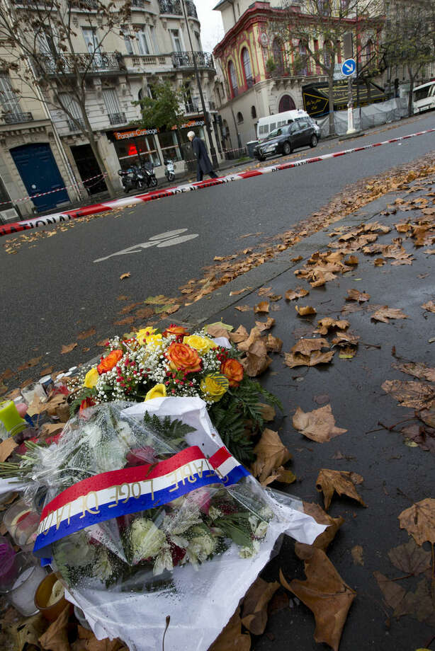 Flowers adorned with a mourning band in the colors of the French flag are seen outside the Bataclan concert hall, in Paris, Tuesday, Nov. 17, 2015. France is demanding security aid and assistance from the European Union in the wake of the Paris attacks and has triggered a never-before-used article in the EU's treaties to secure it. (AP Photo/Peter Dejong)
