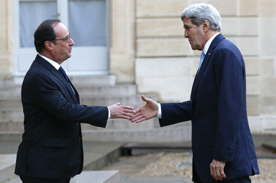 French President Francois Hollande, left, welcomes US Secretary of State John Kerry upon arrival at the Elysee Palace, in Paris, France, Tuesday, Nov. 17, 2015. (AP Photo/Francois Mori)
