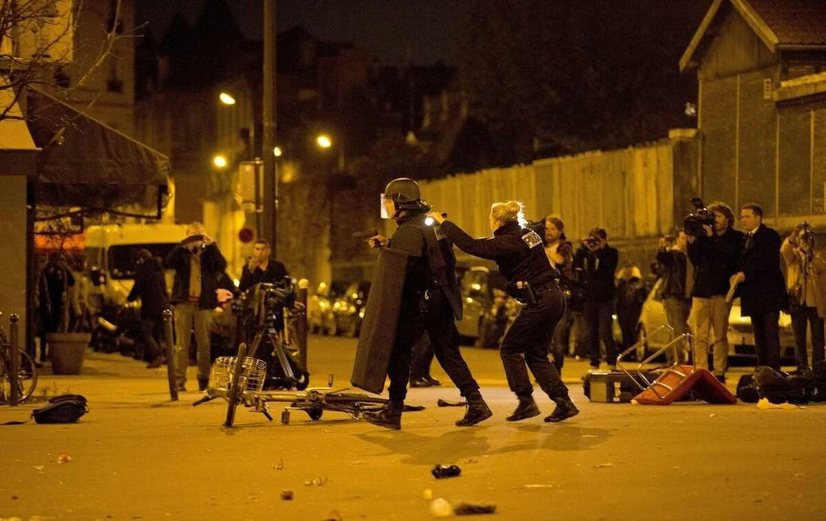 French police secure the perimeter after panic broke out among mourners who payed their respect at the attack sites at restaurant Le Petit Cambodge (Little Cambodia) and the Carillon Hotel in Paris, Sunday, Nov. 15, 2015. Thousands of French troops deployed around Paris on Sunday and tourist sites stood shuttered in one of the most visited cities on Earth while investigators questioned the relatives of a suspected suicide bomber involved in the country's deadliest violence since World War II. (AP Photo/Peter Dejong)