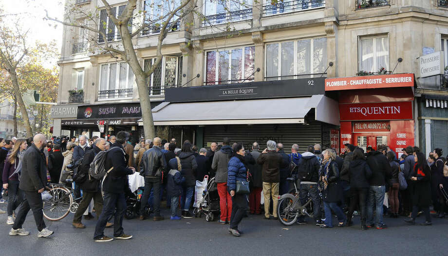 People gather outside the restaurant on Rue de Charonne, Paris, Sunday, Nov. 15, 2015, where attacks took place on Friday. The Islamic State group claimed responsibility for Friday's attacks on a stadium, a concert hall and Paris cafes that left more than 120 people dead and over 350 wounded. (AP Photo/Frank Augstein)