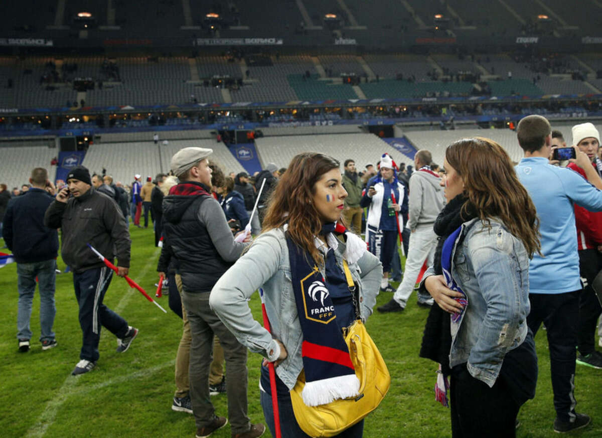 French supporters invade the pitch of the Stade de France stadium at the end of the international friendly soccer match between France and Germany in Saint Denis, outside Paris, Friday, Nov. 13, 2015. Hundreds of people spilled onto the field of the Stade de France stadium after explosions were heard nearby. French President Francois Hollande says he is closing the country's borders and declaring a state of emergency after several dozen people were killed in a series of unprecedented terrorist attacks. (AP Photo/Christophe Ena)