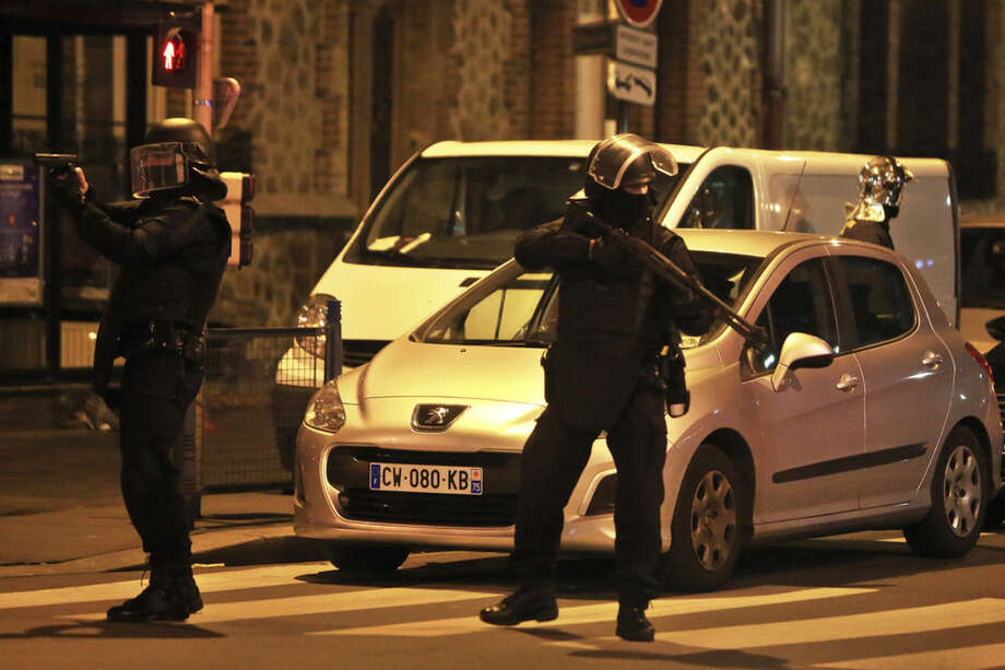 Police forces prepare in St. Denis, a northern suburb of Paris, Wednesday, Nov. 18, 2015. Authorities in the Paris suburb of St. Denis are telling residents to stay inside during a large police operation near France's national stadium that two officials say is linked to last week's deadly attacks. (AP Photo/Thibault Camus)