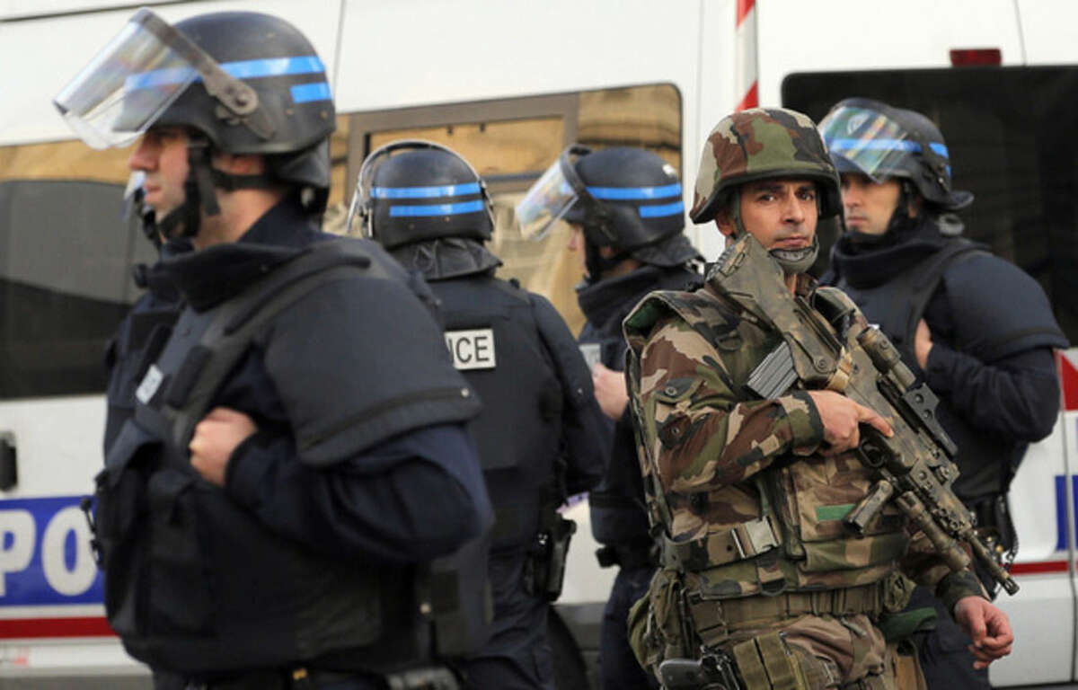 Police forces and soldiers patrol in Saint-Denis, a northern suburb of Paris, Wednesday, Nov. 18, 2015. Police say two suspects in last week's Paris attacks, a man and a woman, have been killed in a police operation north of the capital. Two police officers have been injured in the standoff. Police have said the operation is targeting the suspected mastermind of last week's attacks, believed to be holed up in an apartment in Saint-Denis with several other heavily armed suspects. (AP Photo/Christophe Ena)