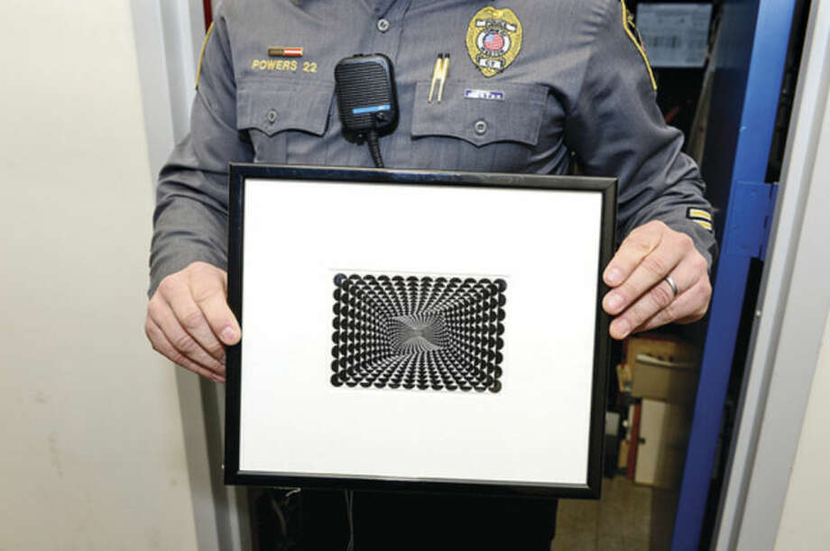 Hour photo / Erik Trautmann Police Chief John Troxel and the Weston Police Department undercovered a larcey ring involving a Weston resident who had tens of thousands of dollars worth of stolen merchandise at his home including fine art like this print by artist Jeffrey Steel (1932) worth $5000.