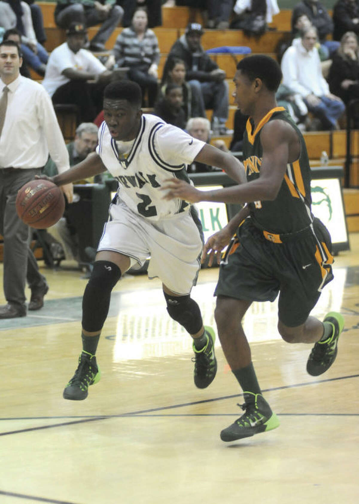 Hour photo/John Nash Norwalk's Zaire Wilson, left, drives past Trinity Catholic's Tremaine Frasier during the fourth quarter of Tuesday's FCIAC boys basketball game at Scarso Gym. The Bears scored a 58-53 victory against the visiting Crusaders.