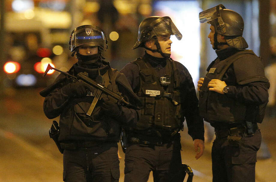 Police forces prepare in St. Denis, a northern suburb of Paris, Wednesday, Nov. 18, 2015. Authorities in the Paris suburb of St. Denis are telling residents to stay inside during a large police operation near France's national stadium that two officials say is linked to last week's deadly attacks. (AP Photo/Christoph Ena)