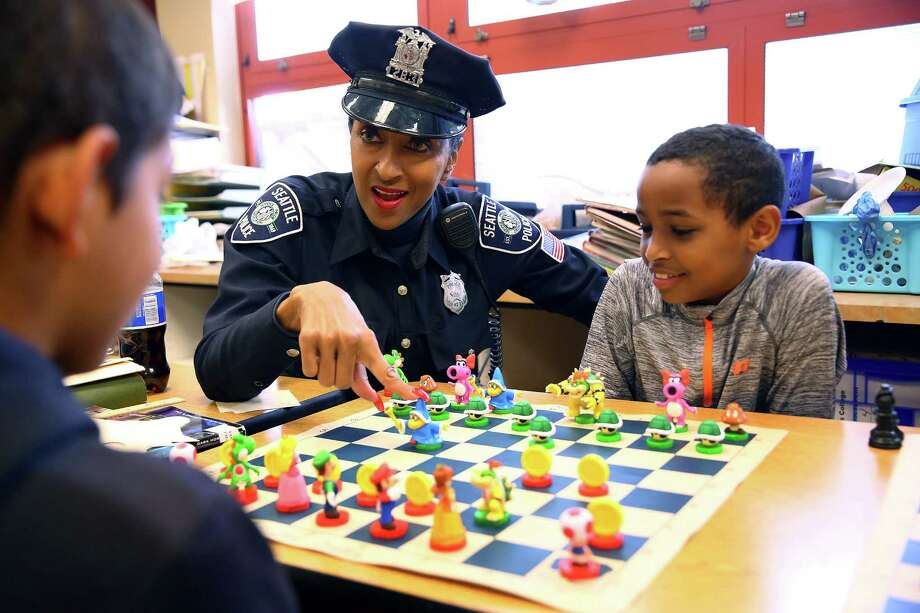 "Detective Denise ""Cookie"" Bouldin talks through a chess game with Van Asselt Elementary students Kaijon Roe, 10,  and Sulayman Hussien, 10, during their lunch break, June 2, 2016. Bouldin teaches chess at Van Asselt and South Shore K-8 several time a week, including stopping in at lunch to play with the students.  Photo: GENNA MARTIN,  SEATTLEPI.COM / SEATTLEPI.COM"
