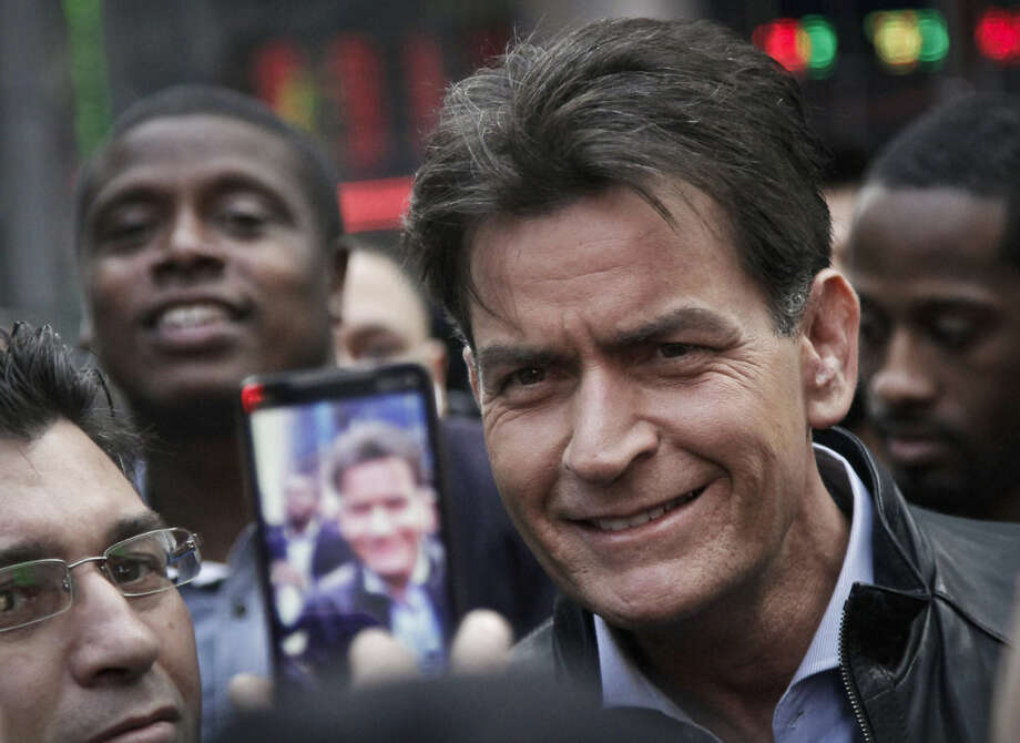 """FILE - In this Monday, Jan. 14, 2013, file photo, actor Charlie Sheen is mobbed for autographs and photos as he makes his way through Times Square in New York. In an interview Tuesday, Nov. 17, 2015, on NBC's """"Today,"""" Sheen said he tested positive for the virus that causes AIDS. (AP Photo/Bebeto Matthews, File)"""