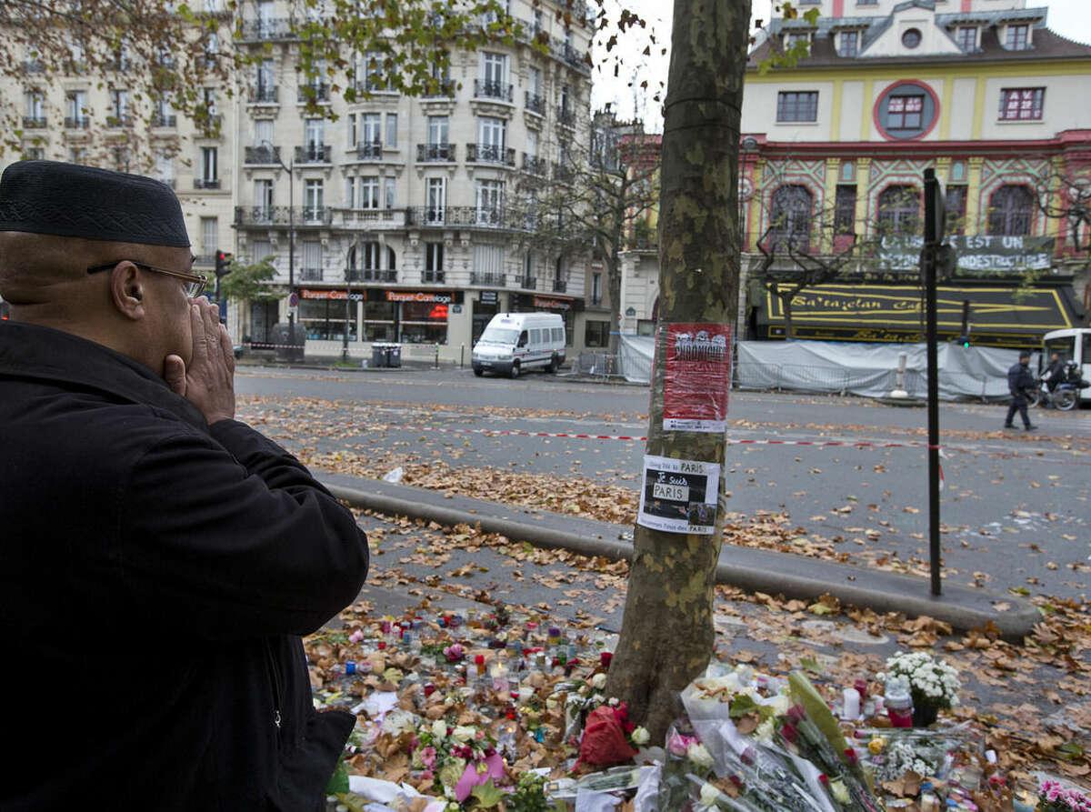 A man prays outside the Bataclan concert hall, rear right, a site of the attacks, which claimed the most victims in Paris, Tuesday, Nov. 17, 2015. France is demanding security aid and assistance from the European Union in the wake of the Paris attacks and has triggered a never-before-used article in the EU's treaties to secure it. (AP Photo/Peter Dejong)