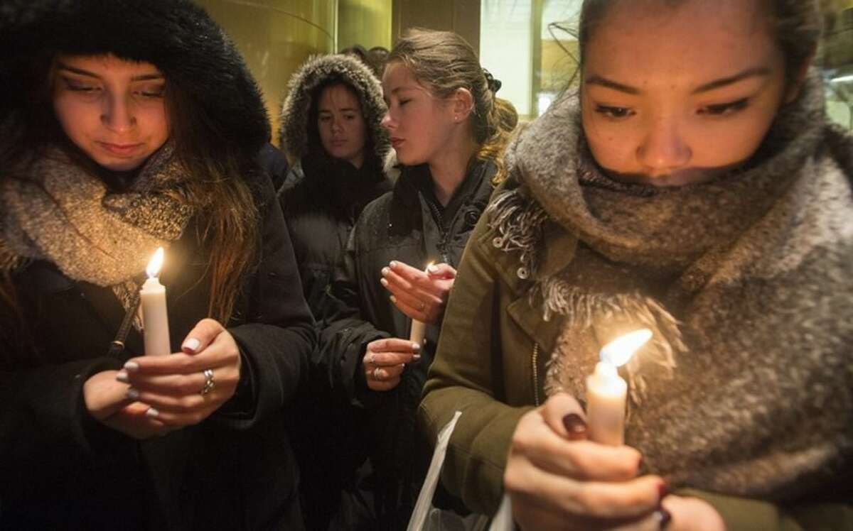 People attend a vigil outside the French consulate in Montreal, Friday, Nov. 13, 2015. Canadian Prime Minister Justin Trudeau offered