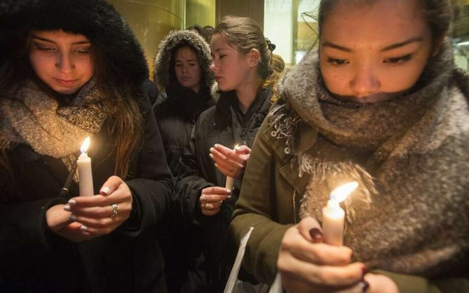 "People attend a vigil outside the French consulate in Montreal, Friday, Nov. 13, 2015. Canadian Prime Minister Justin Trudeau offered ""all of Canada's support"" to France on Friday night in the wake of ""deeply worrying"" terrorist attacks in Paris that killed at least 120 people. (Graham Hughes/The Canadian Press via AP)"
