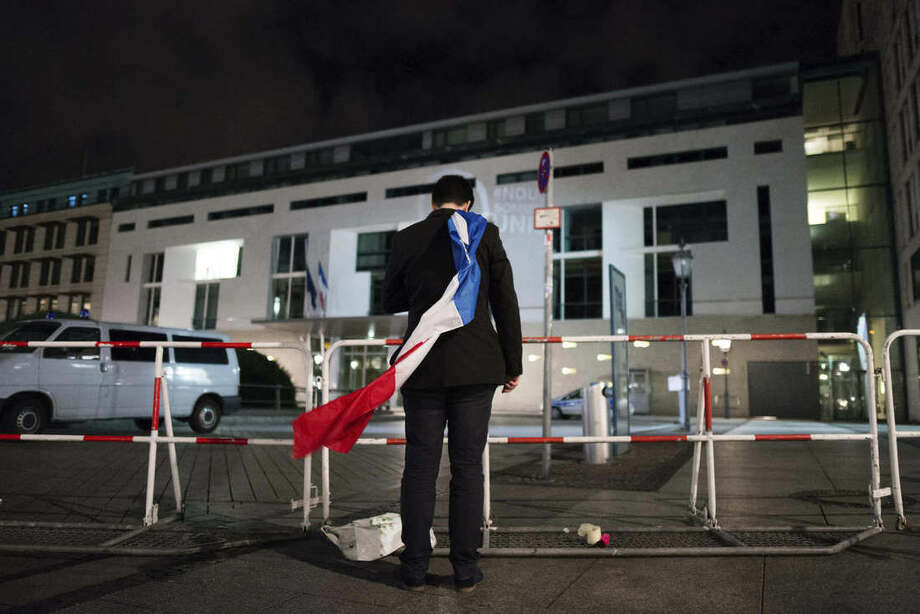 A man is wrapped in a French flag as he puts down flowers in front of the French embassy in Berlin Saturday morning, Nov. 14, 2015. At least 120 people were killed in terror attacks in Paris in the night. (Gregor Fischer/dpa via)