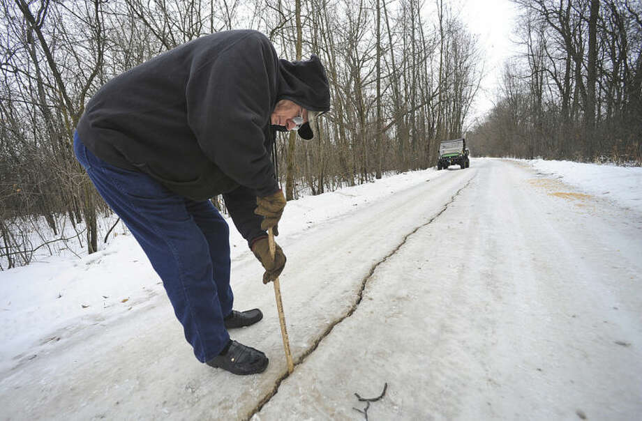 FILE - In this Jan. 11, 2014 photo Dennis Olsen measures a fissure which he said was about an inch wide and at least eight to ten inches deep, in his rural driveway following a frost quake in Waupun, Wis. Known technically as cryoseism, frost quakes are a rare natural phenomena that happen when the temperature drops suddenly, causing moisture in the ground to freeze and expand. They can cause an earthquake-like rumble sometimes with loud, booming noises. (AP Photo/The Reporter, Aileen Andrews, File)
