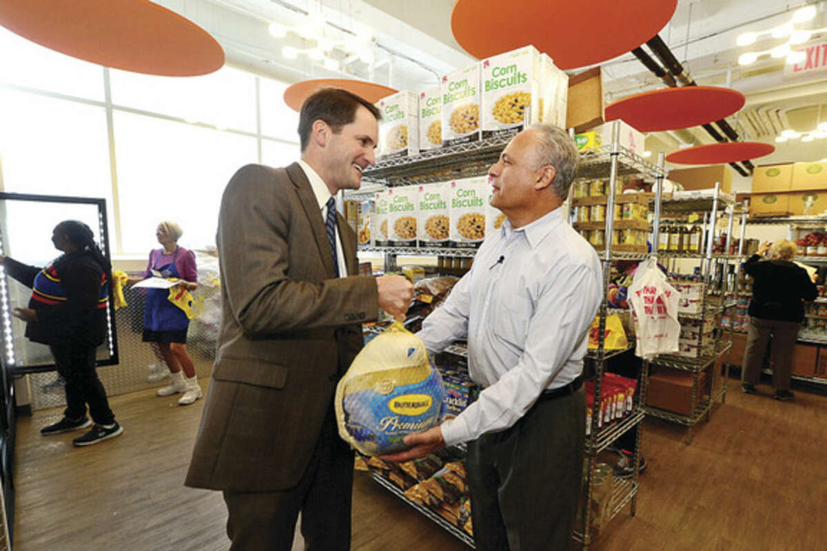 Hour photo/Erik Trautmann U.S. Congressman Jim Himes visits with Covenant House Executive Director John Gutman and donates frozen turkeys Friday at the new Covenant facilities at 174 Richmond Hill Ave. in Stamford. Food pantries like Covenant are in need of extra donations with the holidays around the corner.