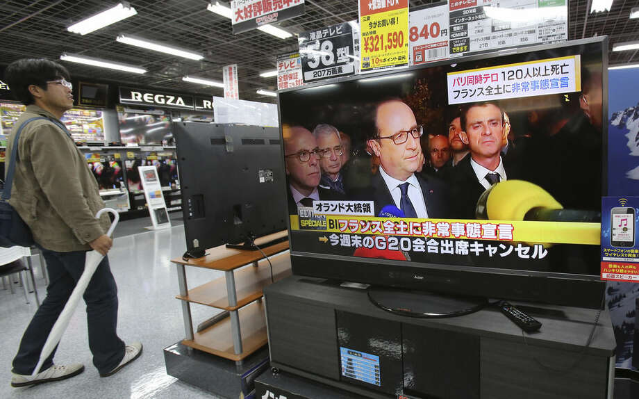 A man walks past a TV screen, which shows French President Francois Hollande speaks about Friday's shootings and explosions in a news program, at Yamada Denki discount store in Tokyo, Saturday, Nov. 14, 2015. A series of attacks targeting young concert-goers, soccer fans and Parisians enjoying a Friday night out at popular nightspots killed more than a hundred of people in the deadliest violence to strike France since World War II. President Hollande condemned it as terrorism and pledged that France would stand firm against its foes. (AP Photo/Koji Sasahara)