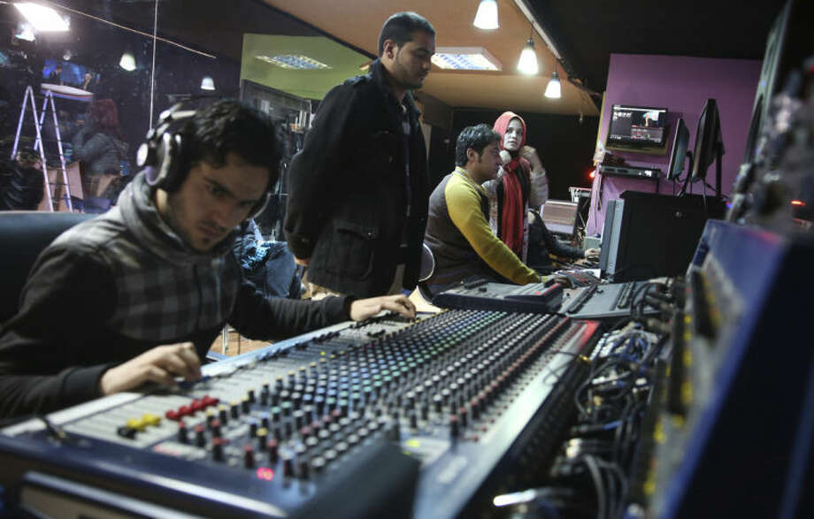 In this Monday, Feb. 3, 2014 photo, Tolo TV staffers work in the Control Room at their office in Kabul, Afghanistan. The proliferation of Afghan media in the past 12 years is one of the most visible bright spots of the fraught project to foster a stable democracy. (AP Photo/Massoud Hossaini)
