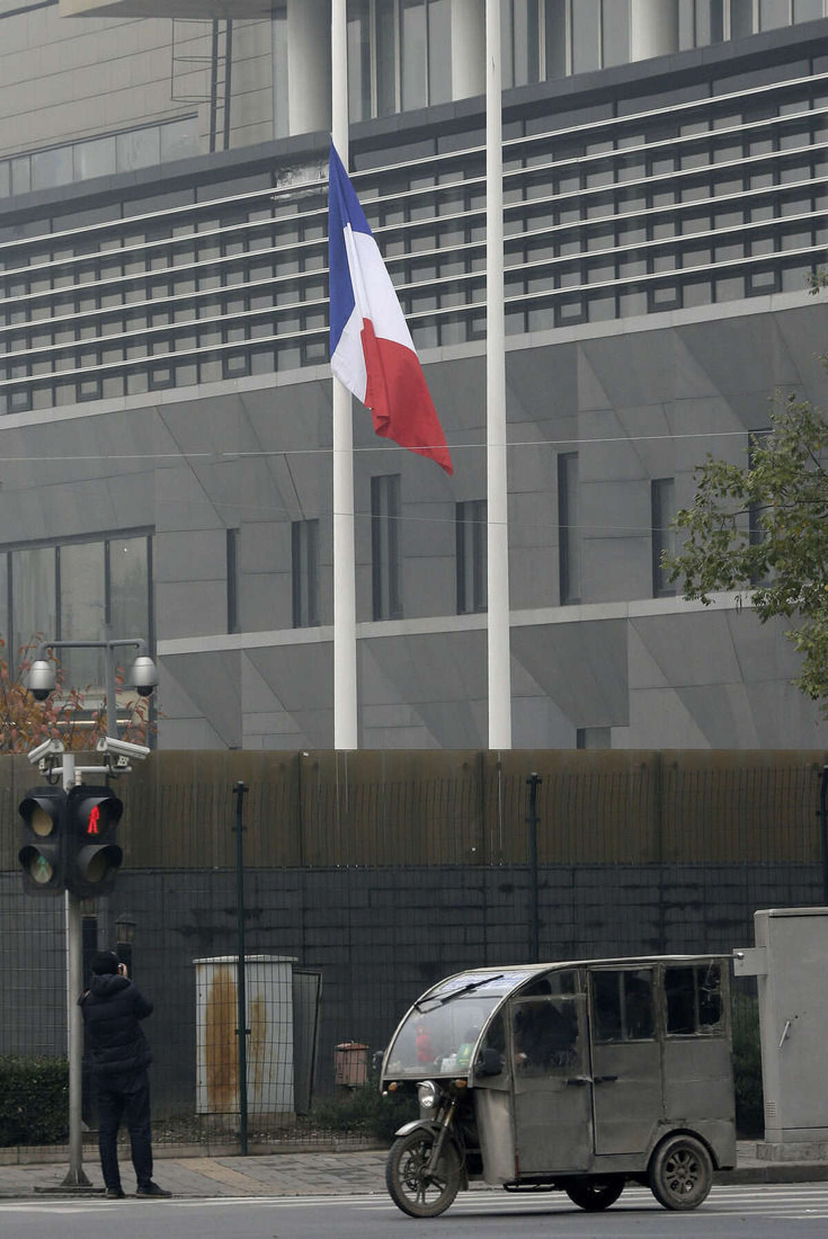 A photographer takes picture of a French national flag fluttering at half-mast to mourn for the victims killed in the Friday's attacks in Paris, France, at the French Embassy compound in Beijing, China, Saturday, Nov. 14, 2015. Foreign Ministry spokesman Hong Lei says China is