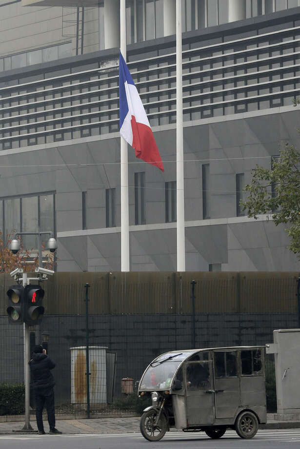 "A photographer takes picture of a French national flag fluttering at half-mast to mourn for the victims killed in the Friday's attacks in Paris, France, at the French Embassy compound in Beijing, China, Saturday, Nov. 14, 2015. Foreign Ministry spokesman Hong Lei says China is ""deeply shocked"" by the attacks and pledged solidarity with France in combating terrorism. ""Terrorism is a common challenge facing humanity. China resolutely supports France in maintaining its national security and stability and in attacking terrorism,"" Hong said. (AP Photo/Andy Wong)"