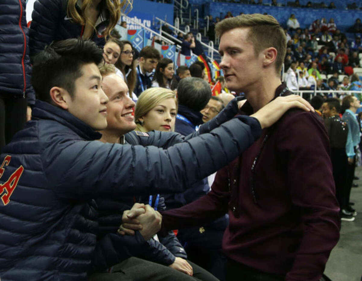 Jeremy Abbott of the United States, right, shakes hands with fellow team members after he competed in the men's team short program figure skating competition at the Iceberg Skating Palace during the 2014 Winter Olympics, Thursday, Feb. 6, 2014, in Sochi, Russia. (AP Photo/Darron Cummings, Pool)