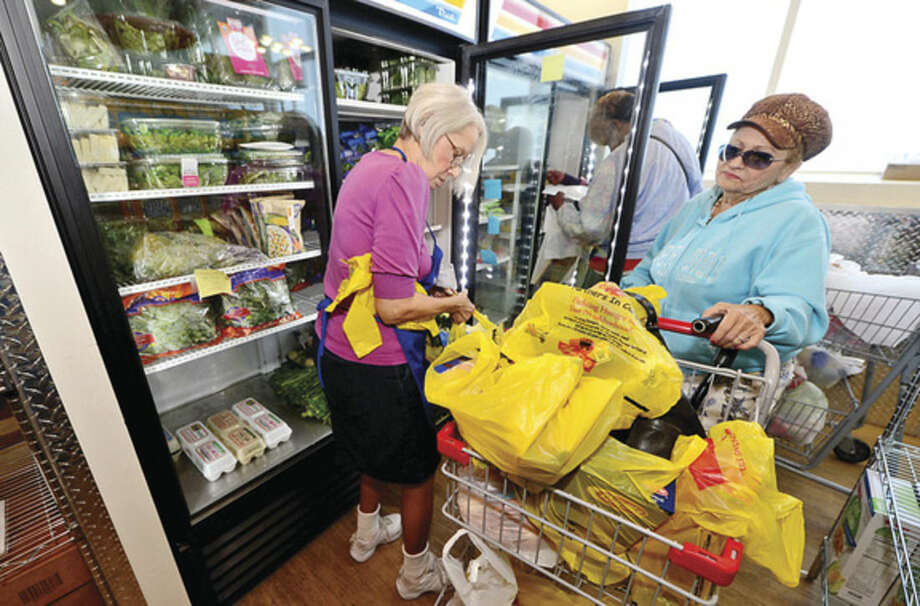 Hour photo / Erik Trautmann Covenant House volunteers help clients load groceries at the new Covenant facilities at 174 Richmond Hill Ave. in Stamford. Food pantries like Covenant are in need of extra donations with the holidays around the corner.