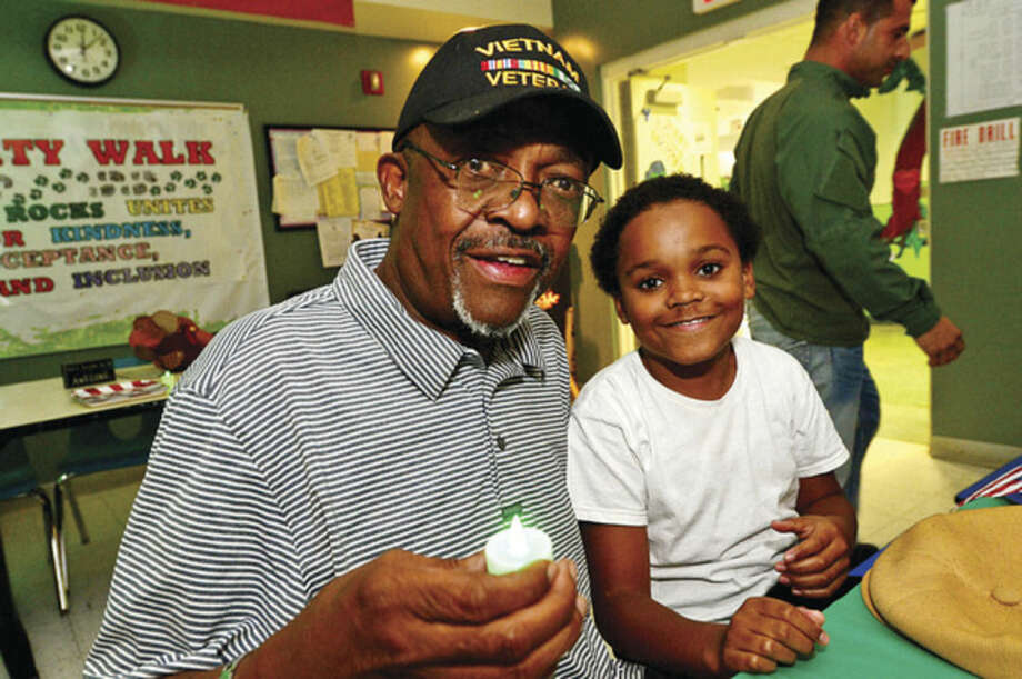 "Hour photo / Erik TrautmannSixth grader Terrence Kitt brings his grandfather, Army vet John Lucas, to lunch Wednesday as West Rocks Middle School honors veterans during their lunch periods as part of the nationwide campaign to ""Green Light a Veteran."""