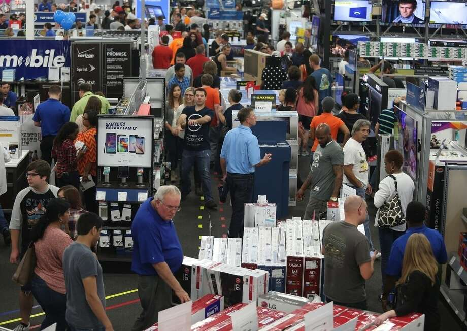 People look at merchandise while holiday shopping at Best Buy on Thursday, Nov. 26, 2015, in Panama City, Fla. Early numbers aren't out yet on how many shoppers headed to stores on Thanksgiving, but it's expected that more than three times the number of people will venture out to shop on the day after the holiday known as Black Friday. (Patti Blake/News Herald via AP) MANDATORY CREDIT